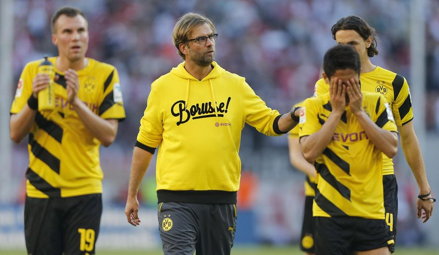 Dortmund's head coach Juergen Klopp, second from left, comforts players after they lost the German first division Bundesliga soccer match between 1.FC Cologne and BvB Borussia Dortmund in Cologne, Germany, Saturday, Oct. 18, 2014. (AP Photo/Frank Augstein)