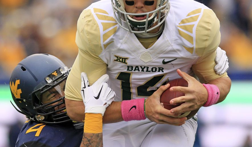 West Virginia's Shaquille Riddick (4) sacks Baylor quarterback Bryce Petty (14) during the first half of an NCAA college football game in Morgantown, W.Va., Saturday, Oct. 18, 2014. West Virginia won 41-27. (AP Photo/Chris Jackson)