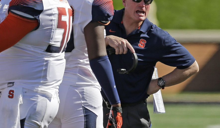 Syracuse head coach Scott Shafer, right, talks to his team during a timeout in the second half of an NCAA college football game against Wake Forest in Winston-Salem, N.C., Saturday, Oct. 18, 2014. Syracuse won 30-7. (AP Photo/Chuck Burton)