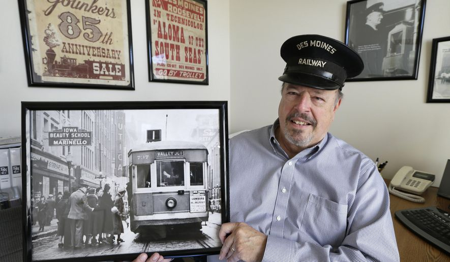 In this Thursday, Oct. 16, 2014 photo, Earl Short holds an old photo showing passengers boarding a streetcar in downtown Des Moines, Iowa, in his Waukee, Iowa, home. The streetcar era ended in Des Moines in 1951, and more than six decades later only about six of the 400 or so former operators are still alive. Many are in their 90s now, and each month three or four of them gather at a suburban restaurant to swap stories about their long-ago jobs as Short, whose father I.J. Short was a streetcar operator, speaks to a larger group of enthusiasts about that period. (AP Photo/Charlie Neibergall)