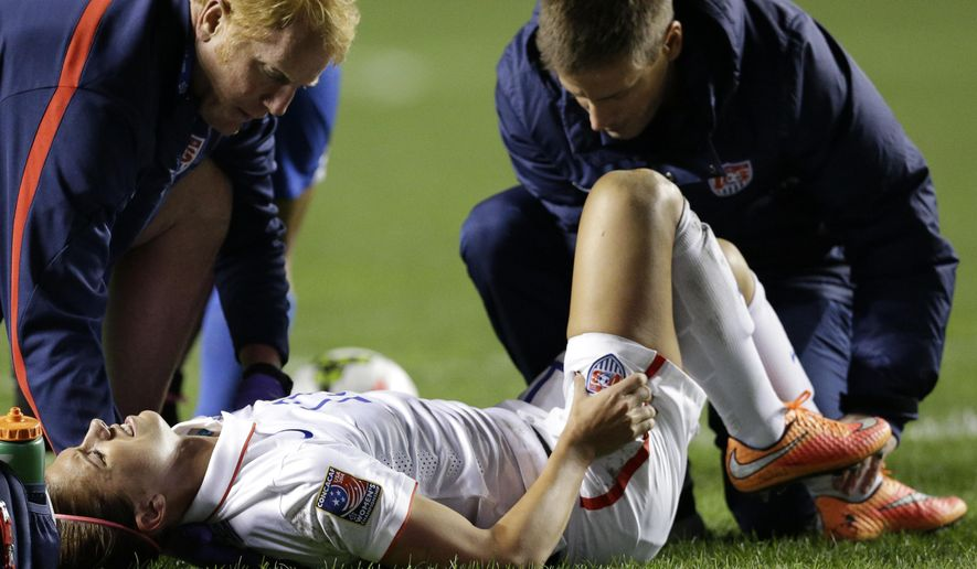 United States' Alex Morgan is checked by team trainer during the first half of a CONCACAF Women's Championship soccer game against Guatemala on Friday, Oct. 17, 2014, in Bridgeview, Ill. (AP Photo/Nam Y. Huh)