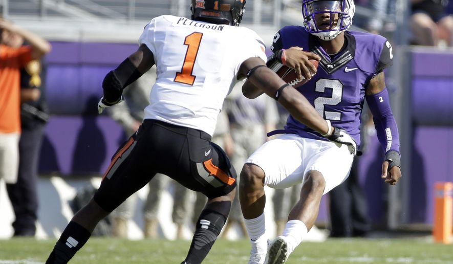 Oklahoma State cornerback Kevin Peterson (1) closes in as TCU quarterback Trevone Boykin (2) prepares to slide after a long run in the first half of an NCAA college football game, Saturday, Oct. 18, 2014, in Fort Worth, Texas. (AP Photo/Tony Gutierrez)