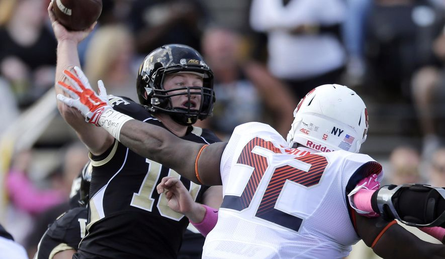 Wake Forest's John Wolford (10) throws a pass under pressure from Syracuse's Eric Crume (52) during the first half of an NCAA college football game in Winston-Salem, N.C., Saturday, Oct. 18, 2014. (AP Photo/Chuck Burton)