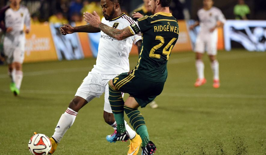 Real Salt Lake forward Robbie Findley,left, and Portland Timbers defender Liam Ridgewell (24) battle for a ball during the first half of an MLS soccer game on Friday, Oct. 17, 2014, in Portland, Ore. (AP Photo/Steve Dykes)