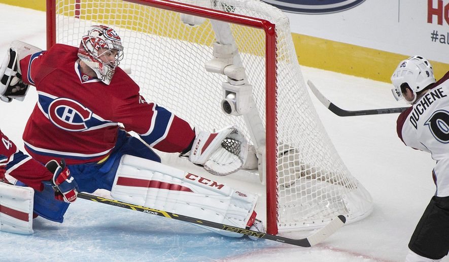 Montreal Canadiens goaltender Carey Price makes a save against Colorado Avalanche's Matt Duchene, right, during the first period of an NHL hockey game, Saturday, Oct. 18, 2014  in Montreal. (AP Photo/The Canadian Press, Graham Hughes)