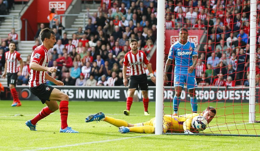 Southampton's Jack Cork, left, scores past Sunderland's Vito Mannone during their English Premier League soccer match at St. Mary's Stadium, Southampton, England, Saturday, Oct. 18, 2014. (AP Photo/Chris Ison, PA Wire)       UNITED KINGDOM OUT   -   NO SALES    -   NO ARCHIVES