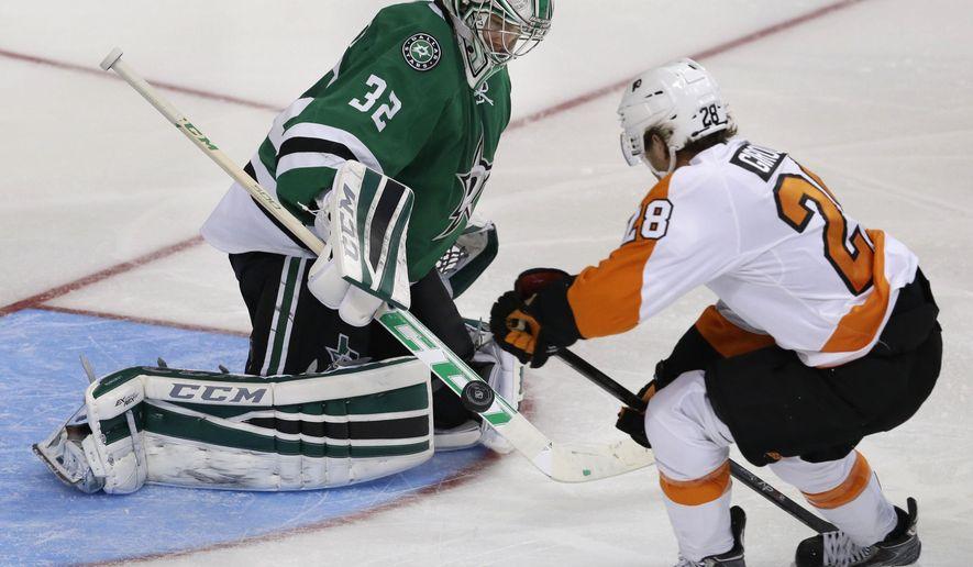 Dallas Stars goalie Kari Lehtonen (32) blocks the puck against Philadelphia Flyers center Claude Giroux (28) during the second period of an NHL hockey game Saturday, Oct. 18, 2014, in Dallas. (AP Photo/LM Otero)