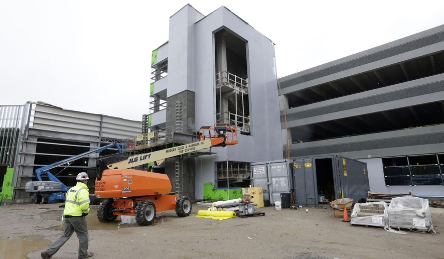 In this Oct. 1, 2014 photo, a worker walks toward the planned parking garage of the Plainridge Park Casino, under construction adjacent to the Plainridge Racecourse harness racing track in Plainville, Mass. Voters will decide in the Nov. 4 election whether to repeal a 2011 law that opened the door for casinos in the state. (AP Photo/Steven Senne)