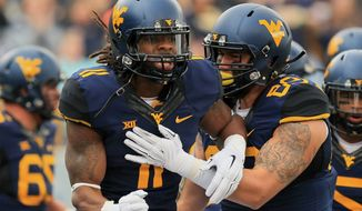 West Virginia's Kevin White (11) celebrates a touchdown with Dustin Garrison (29) during the first quarter of an NCAA college football game against Baylor in Morgantown, W.Va., Saturday, Oct. 18, 2014. West Virginia won 41-27. (AP Photo/Chris Jackson)