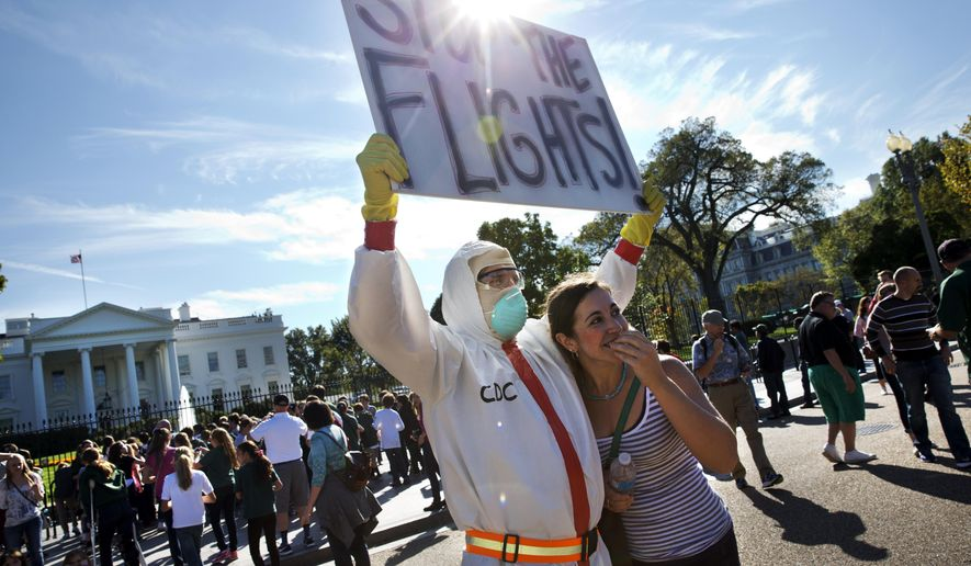 In this Oct. 17, 2014, photo, Jeff Hulbert, left, of Annapolis, Md., protests U.S. handling of Ebola cases, as Mary Wills, right, of Cleveland, playfully covers her face while taking a photo with Hulbert, outside of the White House. A ban on travel from West Africa might seem like a simple and smart response to the frightening Ebola outbreak there. It's become a central demand of Republicans on Capitol Hill and some Democrats, and is popular with the public. But health experts are nearly unanimous in saying it's a bad idea that could backfire. (AP Photo/Jacquelyn Martin)