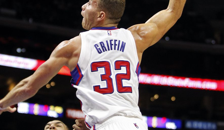 Los Angeles Clippers forward Blake Griffin (32) goes in for a dunk over Utah Jazz center Rudy Gobert (27), of France, during the first half of an NBA preseason basketball game Friday, Oct. 17, 2014, in Los Angeles. (AP Photo/Alex Gallardo)