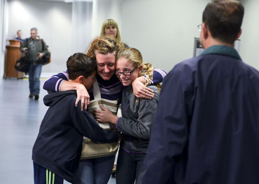 Joy Bauer, left, hugs her children Ethan and Emily Bauer at Gerald R. Ford Airport after her plane from Dallas-Fort Worth airport was temporarily detained after a few passengers fell ill on Friday, Oct. 17, 2014 in Grand Rapids, Mich. (AP Photo/Grand Rapids Press, Emily Rose Bennett)