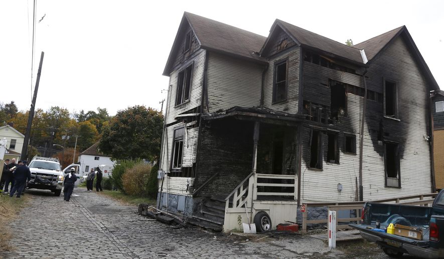 Emergency workers gather in front of the house in McKeesport, Pa. where a fire killed six members of a family, four of them children, and left another in the hospital in critical condition on Saturday, Oct. 18, 2014. (AP Photo/Keith Srakocic)