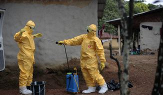 In this Sept. 30, 2014, file photo, Gordon Kamara, left, is sprayed by Konah Deno after they loaded six patients suspected to have been infected by the Ebola virus into their ambulance in the village of Freeman Reserve, about 30 miles north of Monrovia, Liberia. *AP Photo/Jerome Delay, File)
