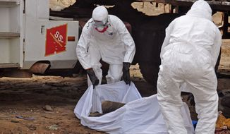 FILE- In this Aug. 12, 2014, file photo, the body of a man found in the street, suspected of dying from the Ebola virus is covered and removed by health workers, in the capital city of Monrovia, Liberia. (AP Photo/Abbas Dulleh, File)