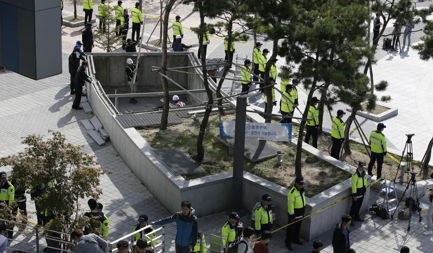 Police officers stand around a collapsed ventilation grate in Seongnam, South Korea, Saturday, Oct. 18, 2014. Sixteen people watching an outdoor pop concert in South Korea fell 20 meters (60 feet) to their deaths Friday when a ventilation grate they were standing on collapsed, officials said. (AP Photo/Lee Jin-man)