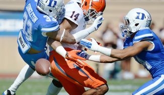 Virginia wide receiver Andre Levrone (14)  can't hold on to the ball under pressure from Duke's Deondre Singleton (33) and Bryon Fields during an NCAA college football game Saturday, Oct. 18, 2014, in Durham, N.C. (AP Photo/The Herald-Sun, Bernard Thomas)