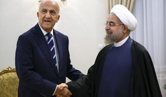 "Lebanese Defense Minister Samir Moqbel, left, shakes hands with Iran's President Hassan Rouhani at his office in Tehran, Iran, Sunday, Oct. 19, 2014. Moqbel also met other Iranian officials including Ali Shamkhani, Secretary of the Supreme National Security Council. ""Iran is ready to transfer its experience in order to improve security in Lebanon and the region, and to combat terrorists,"" Shamkhani said during a meeting with Moqbel in Tehran on Sunday. (AP Photo/Ebrahim Noroozi)"