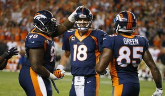 Denver Broncos quarterback Peyton Manning (18) is greeted by Terrance Knighton (98) and Virgil Green (85) after throwing his 509th career touchdown pass during the first half of an NFL football game against the San Francisco 49ers, Sunday, Oct. 19, 2014, in Denver.  (AP Photo/Jack Dempsey)