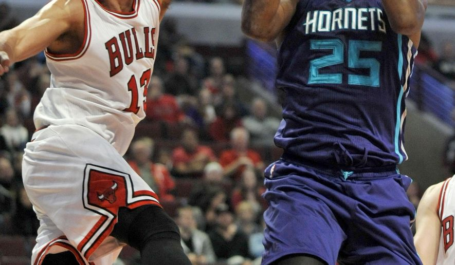 Charlotte Hornets' Al Jefferson (25) goes up for a shot against Chicago Bulls' Joakim Noah (13) during the first half of an NBA basketball game in Chicago, Sunday, Oct. 19, 2014. (AP Photo/Paul Beaty)