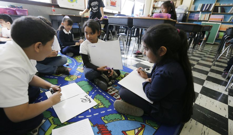 In this Sept. 19, 2014, photo, Hispanic students work on reading skills at the Detroit Public Schools' Academy of the Americas in Detroit. The school is expecting a 9 percent enrollment increase, which would push the number to about 800, said principal Nicholas Brown. Students take most of their classes beginning in Spanish in the earliest grades and phase in more English in later grades. (AP Photo/Carlos Osorio)