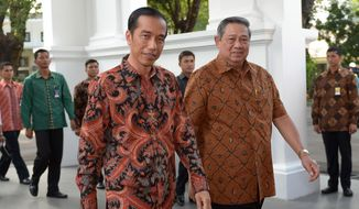 Outgoing Indonesian President Susilo Bambang Yudhoyono, right, walks with President-elect Joko Widodo upon arrival prior to a tour of the presidential palace in Jakarta, Indonesia, Sunday, Oct. 19, 2014. Widodo, popularly known as Jokowi, will be inaugurated as the country's new president on Monday, Oct. 20. (AP Photo/Adek Berry, Pool)
