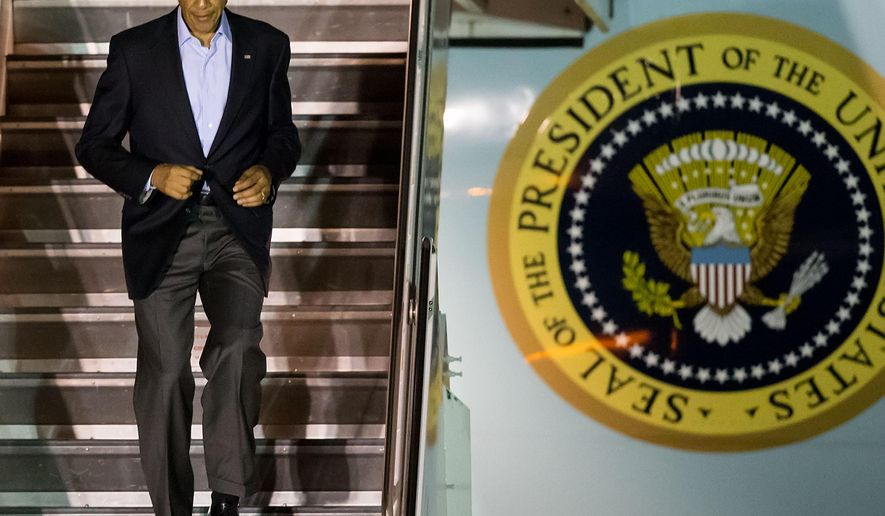 President Barack Obama walks off Air Force One after arriving at O'Hare International Airport in Chicago on Sunday, Oct. 19, 2014. (AP Photo/Andrew A. Nelles)