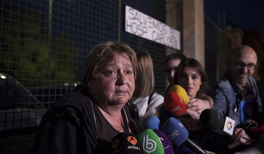 Teresa Mesa, left, spokesperson of Ebola patient Teresa Romero speaks to the media in front of the Carlos III Hospital in Madrid, Spain, Sunday, Oct. 19, 2014. Spain says a test has shown a nursing assistant who became infected with Ebola is now clear of all traces of the virus. A blood test has revealed that Teresa Romero's immune system has eliminated the virus from her body, according to a statement released by Prime Minister Mariano Rajoy's office late Sunday. Romero, 44, had treated two patients who died of Ebola at Carlos III hospital. The first, Miguel Pajares, contracted the disease in Liberia and died on Aug. 12 despite having been treated with the experimental drug ZMapp. The second was Manuel Garcia Viejo who died, aged 69, on Sept. 25. (AP Photo/Gabriel Pecot)