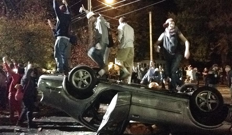 "Colin Flaherty rejects equating ""white college kids starting bonfires"" with Ferguson protestors ""attacking police and throwing molotov cocktails."" Above: Keene, N.H. pumpkin festival. (AP Photo/The Boston Globe, Jeremy Fox)"