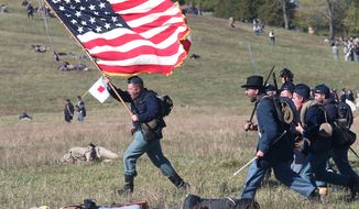 A Union re-enactor carrying a flag yells as he charges at retreating Confederates during the 150th anniversary of the Battle of Cedar Creek event in Middletown, Va. Sunday, Oct. 19, 2014. The re-enactment is held on the same field as the battle on Oct. 19, 1864. (AP Photo, The Winchester Star, Jeff Taylor)