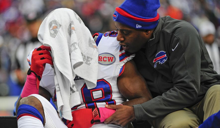 Buffalo Bills running back C.J. Spiller (28) is comforted as he is carted off the field after being injured during the first half of an NFL football game against the Minnesota Vikings, Sunday, Oct. 19, 2014, in Orchard Park, N.Y.  (AP Photo/Gary Wiepert)