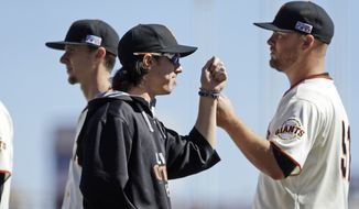 San Francisco Giants pitcher Tim Lincecum (55) pumps fists with teammates before Game 3 of baseball's NL Division Series against the Washington Nationals in San Francisco, Monday, Oct. 6, 2014. (AP Photo/Ben Margot)