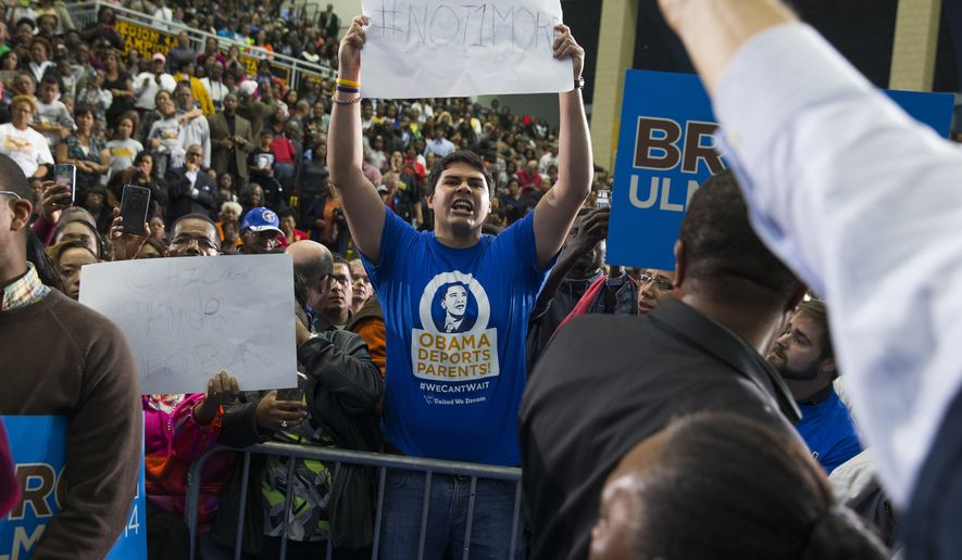A demonstrator shouting about immigration policy interrupts President Barack Obama during a campaign rally for Maryland gubernatorial candidate Anthony Brown at Wise High School, on Sunday, Oct. 19, 2014, in Upper Marlboro, Md. (AP Photo/Evan Vucci)