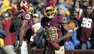 Washington Redskins wide receiver Pierre Garcon (88) celebrates hist touchdown during the second half of an NFL football game against the Tennessee Titans, Sunday, Oct. 19, 2014, in Landover, Md. (AP Photo/Mark E. Tenally)