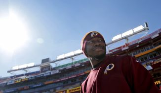 Washington Redskins quarterback Robert Griffin III (10) walks on the field before an NFL football game against the Tennessee Titans, Sunday, Oct. 19, 2014, in Landover, Md. (AP Photo/Pablo Martinez Monsivais)