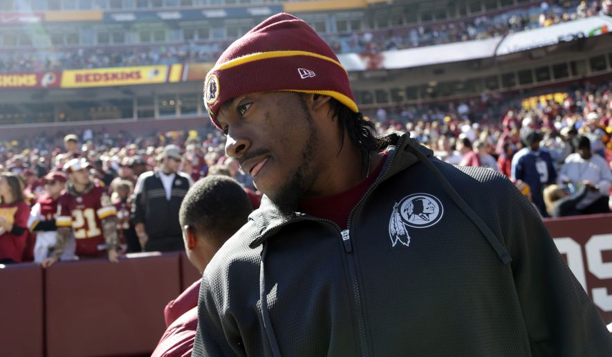 Washington Redskins quarterback Robert Griffin III (10) heads to the sidelines before the start of an NFL football game against the Tennessee Titans, Sunday, Oct. 19, 2014, in Landover, Md. (AP Photo/Pablo Martinez Monsivais)