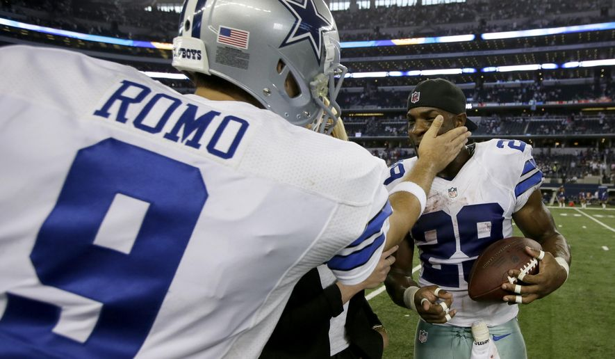 Dallas Cowboys' Tony Romo (9) taps running back DeMarco Murray (29) on the cheek after handing him the ball after their NFL football game against the New York Giants, Sunday, Oct.  19, 2014, in Arlington, Texas. The Cowboys won 31-21. (AP Photo/Brandon Wade)