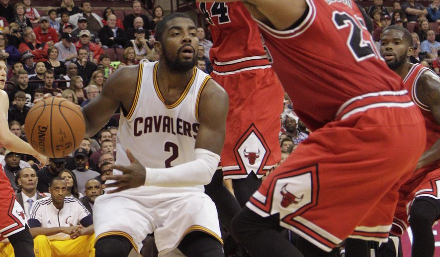 Cleveland Cavaliers' Kyrie Irving, left, looks for an open pass between Chicago Bulls' Taj Gibson, right, and Nikola Mirotic, of Yugoslavia, during the second quarter of an NBA preseason basketball game Monday, Oct. 20, 2014, in Columbus, Ohio. (AP Photo/Jay LaPrete)