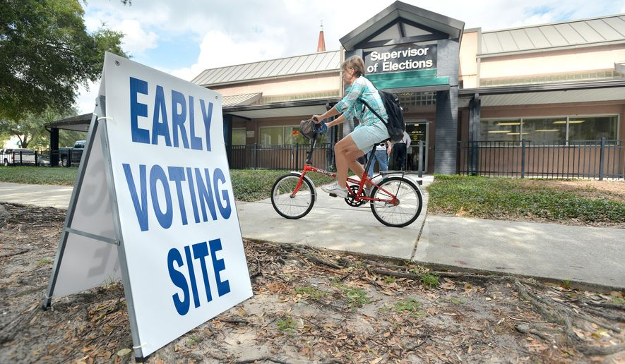 A cyclist passes the Supervisor of Elections office in Jacksonville, Fla. Early voting for the November 4 elections began on Monday, Oct. 20, 2014 in Duval County. (AP Photo/The Florida Times-Union, Bruce Lipsky)