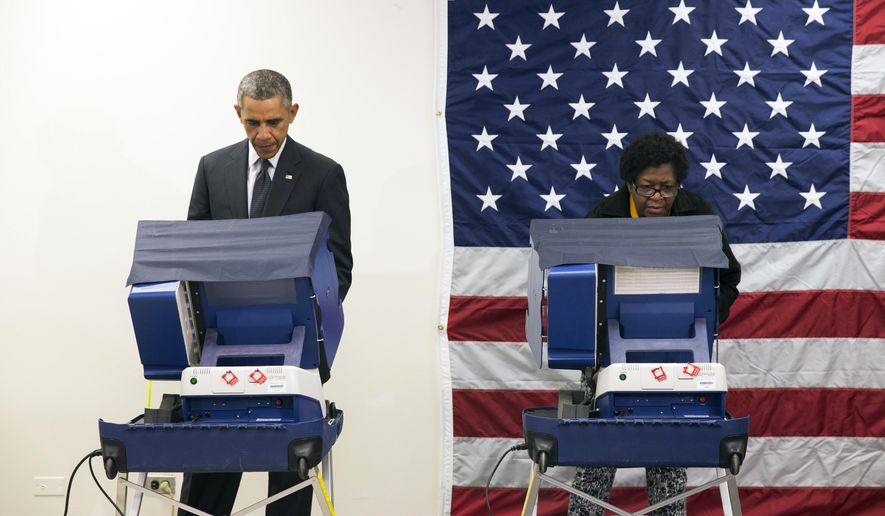 President Barack Obama, left, votes early for the midterm election at the Dr. Martin Luther King Community Service Center Monday, Oct. 20, 2014, in Chicago. Obama took a break from campaigning for Gov. Pat Quinn, D-Ill., to cast an early ballot for the election. (AP Photo/Evan Vucci)