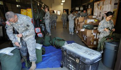 Soldiers from the 35th Theater Tactical Signal Brigade pack their gear as they prepare for deployment to west Africa to aid against the spread of the Ebola virus in Fort Gordon, Ga., Monday, Oct. 20, 2014. (AP Photo/The Augusta Chronicle, Michael Holahan)