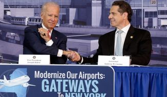 Vice President Joe Biden, left, shakes hands with New York Gov. Andrew Cuomo, in a hangar of the Vaughn College of Aeronautics and Technology, in New York,  Monday, Oct. 20, 2014, during a presentation to discuss the need to improve New York's airports. Biden joined Cuomo as the governor announced a design competition to modernize and improve New York City's John F. Kennedy and LaGuardia Airports. (AP Photo/Richard Drew)