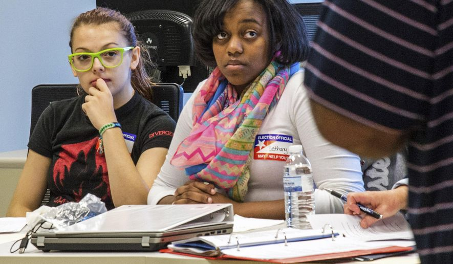 In this Oct. 8, 2014 photo, Nicole Wheatley, left, and Bethany Peppers, both 16, from Urbana, Ill., listen to director of training Matthew Grandone during an election judge class at Brookens Administration Center in Urbana. Dozens of high school students in central Illinois will serve as election judges at the polls this Election Day. In Illinois, junior or senior high school students are eligible to be election judges if they have a 3.0 GPA, have permission from a parent or guardian and their high school principal and go through training. (AP Photo/The News-Gazette, Robin Scholz)  MANDATORY CREDIT