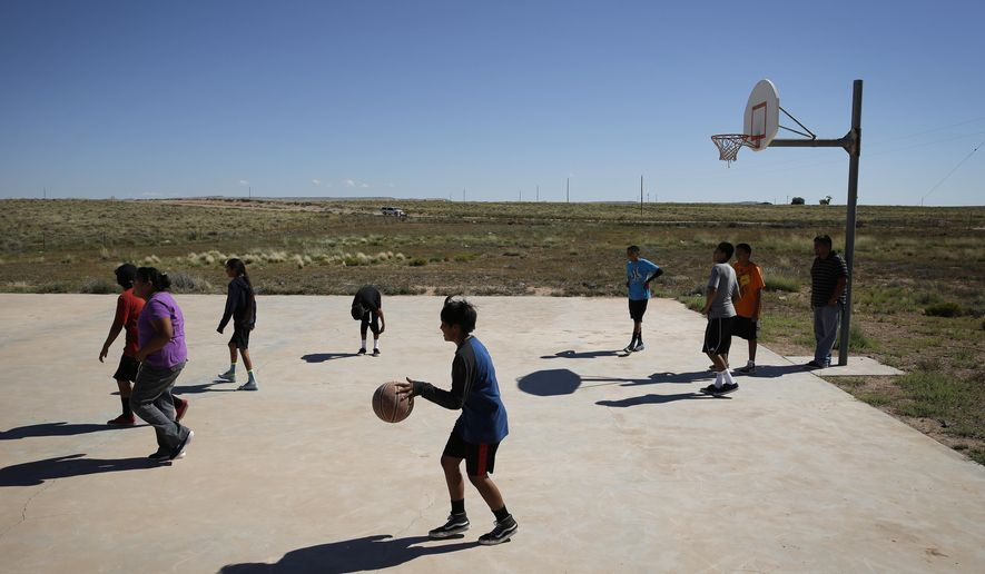 In this photo taken Sept. 25, 2014, seventh and eighth grade students play basketball at the Little Singer Community School in Birdsprings, Ariz., on the Navajo Nation. The school is miles from any gas station or paved road. The Obama administration is pushing ahead with a plan to improve the schools that gives tribes more control. But the endeavor is complicated by disrepair of so many buildings, not to mention a federal legacy dating to the 19th century that for many years forced Native American children to attend boarding schools. (AP Photo/John Locher)
