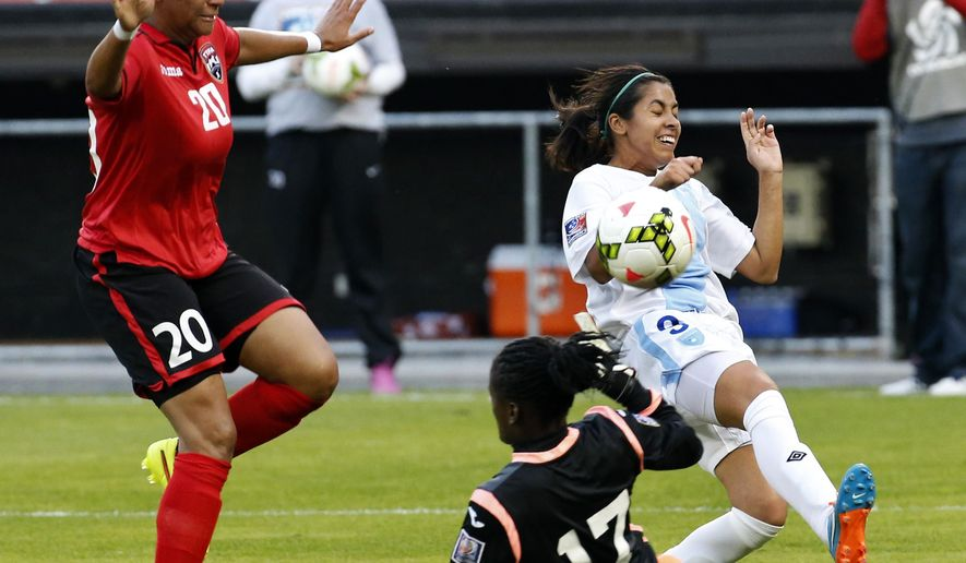 Trinidad & Tobago defender Lauren Hutchinson (20) defends as goalkeeper Tenesah Palmer blocks a shot by Guatemala forward Ana Lucia Martinez (9) during the first half of a CONCACAF soccer match, at RFK Stadium, Monday, Oct. 20, 2014, in Washington. (AP Photo/Alex Brandon)