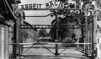 FILE - This undated file photo shows the main gate of the Auschwitz death camp complex in occupied-Poland. The writing over the gate reads 'Arbeit Macht Frei' (Work Sets You Free). An Associated Press investigation found dozens of suspected Nazi war criminals and SS guards collected millions of dollars in Social Security payments after being forced out of the United States. (AP Photo, File)