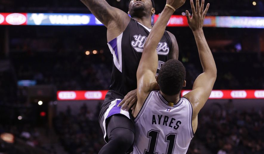 Sacramento Kings' DeMarcus Cousins, left, drives to the basket over San Antonio Spurs' Jeff Ayres (11) during the second half of an NBA preseason basketball game, Monday, Oct. 20, 2014, in San Antonio. (AP Photo/Eric Gay)
