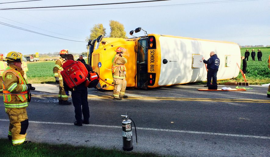 Firefighters work the scene of an overturned school bus on Monday, Oct. 20, 2014 in Paradise, Pa. Authorities in Lancaster County said the crash of the bus carrying special needs students just before 8:30 a.m. in Paradise Township also involved a dump truck and a tractor-trailer. (AP Photo/Intelligencer Journal, Blaine Shahan)