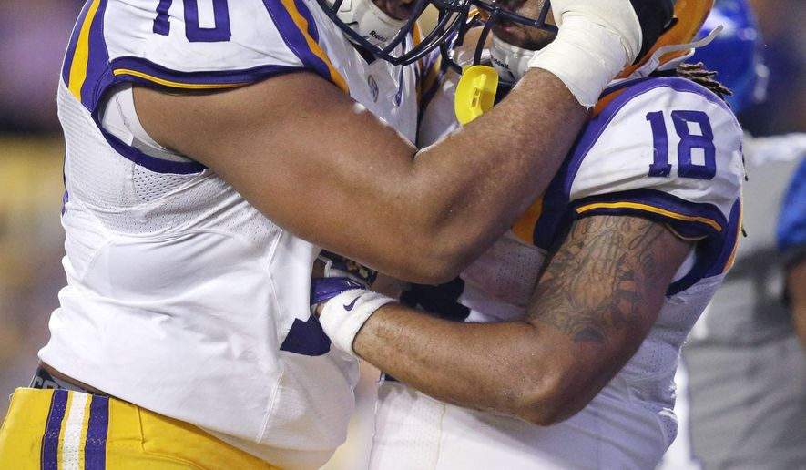 LSU running back Terrence Magee (18) celebrates his touchdown carry with offensive tackle La'el Collins (70) in the second half of an NCAA college football game against Kentucky in Baton Rouge, La., Saturday, Oct. 18, 2014. LSU won 41-3. (AP Photo/Gerald Herbert)