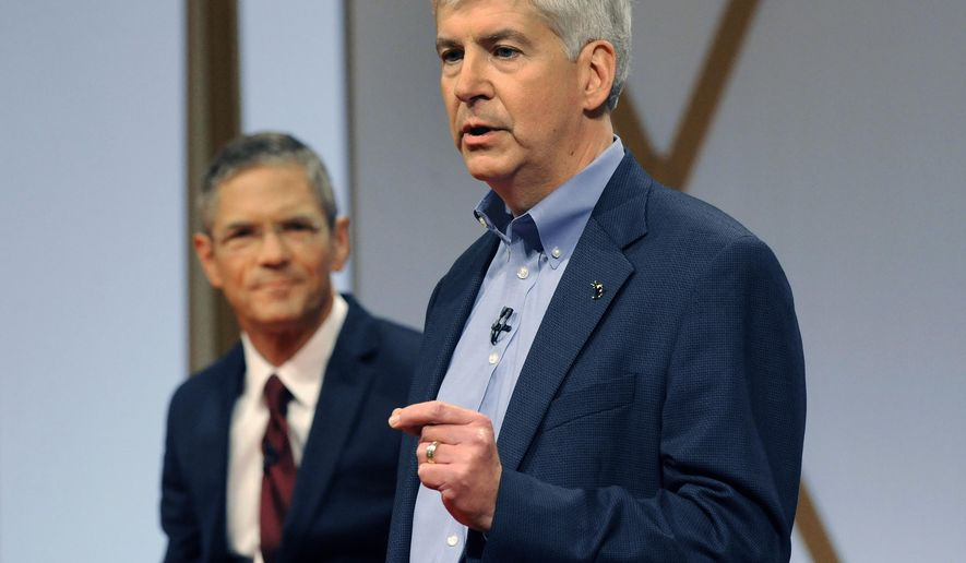 ADVANCE FOR RELEASE SUNDAY, OCT. 19, 2014, AND THEREAFTER- FILE- In an Oct. 12, 2014 file photo, Michigan Gov. Rick Snyder, right, addresses the crowd as Democratic challenger Mark Schauer listens during a town hall meeting in Detroit. Schauer is centering his populist message against the governor around a 3-year-old tax overhaul that lowered the burden on business but raised it on individuals. (AP Photo/Jose Juarez, File)
